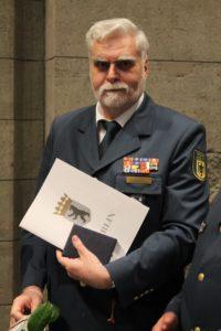 Ulrich Vogel mit Urkunde und Ehrenzeichen. Foto: THW/Sascha Barnewske